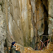 A hiker resting athe entrance to the cave shrines of Khao Tham Talu in Ratchaburi province, Thailand