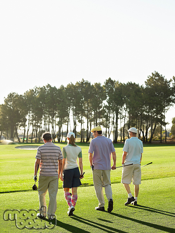 Four young golfers walking on course back view