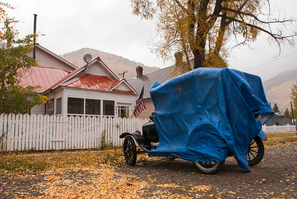 A vinatge automobile sits covered with tarps on one of Silverton's side streets.