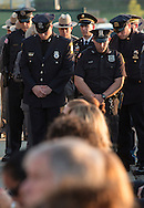 Goshen, New York - Police officers bow their heads at the end of the Orange County Law Enforcement Officer Memorial Service on May 8, 2015, at the entrance of the Orange County Courthouse. The memorial service honors the memory of the members of the Orange County law enforcement community that died in the line of duty. The service also pays tribute the families and loved ones left behind for their courage, dignity and perseverance.