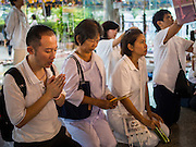 11 JANUARY 2015 - BANGKOK, THAILAND:  People pray during a three day retreat to practice the Eight Precepts at Wat Dhamma Mongkol in Bangkok. Buddhist precepts are moral guidelines Buddhists follow rather than commandments in the Christian sense of the word. As Buddhists develop in the Dhamma, they find that the Precepts grounds their practice. One cannot waver and purposely break any of the Precepts. The Eight Precepts are typically also practiced during intensive meditation retreats of one day or longer. Wat Dhamma Mongkol, (pronounced 'Dhammamongkon') is on the edge of Bangkok, and visible from a number of places, especially from the elevated expressways around the city. The temple was started in the early 1960s by a revered monk who had spent more than 20 years in a forest retreat. The 95 meter high tower, completed in 1985, is a modern rendition of the tower that now marks the place of the Buddha's enlightenment in Bodhgaya, India. There are classrooms, a museum and meditation area inside the tower. The largest Buddha statue carved from a single piece of jade is on the temple grounds.   PHOTO BY JACK KURTZ