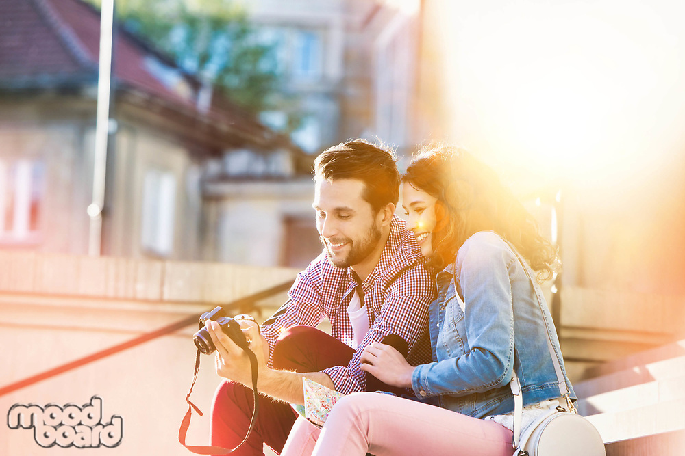 Portrait of handsome young man showing pictures on camera to his beautiful girlfriend while sitting against museum with lens flare in background