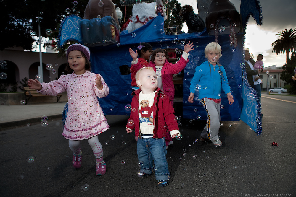 Jake Leonhardt, 15 months, plays among a swarm of bubbles behind a float after watching his first La Jolla Christmas Parade.