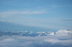 Mountains peak through the clouds just south of the Arctic Circle near Fairbanks, Alaska.