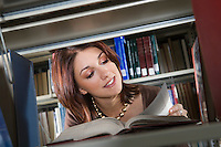Female university student reading in library