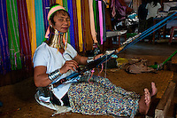 Kayan woman weaving, Red Karen peoples, with gold hoops on her neck.