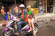 14 APRIL 2013 - BANGKOK, THAILAND:   A woman on a motorcycle taxi rides through a water fight on Soi Nana on April 14, 2013 in Bangkok, Thailand. The Songkran festival is celebrated in Thailand as the traditional New Year's Day from 13 to 15 April. The throwing of water originated as a way to pay respect to people and is meant as a symbol of washing all of the bad away. PHOTO BY JACK KURTZ