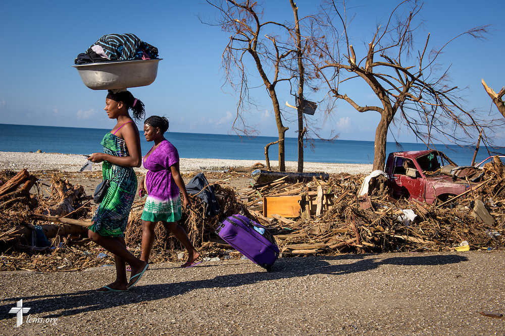 Women carry supplies on the road littered with debris caused by Hurricane Matthew on Wednesday, Oct. 12, 2016, in Port-Salut, Haiti. LCMS Communications/Erik M. Lunsford