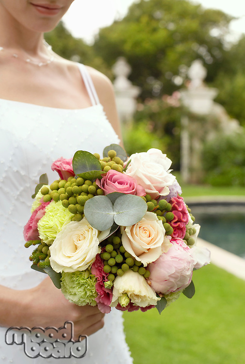 Mid adult bride in garden holding bouquet mid section