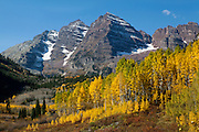 A crisp, clear fall day highlights the beauty of Maroon Bells. Maroon Bells consist of two peaks, Maroon Peak (center) and North Maroon Peak (right) above 14,000 feet.  Turning Aspen surround the peaks with color.