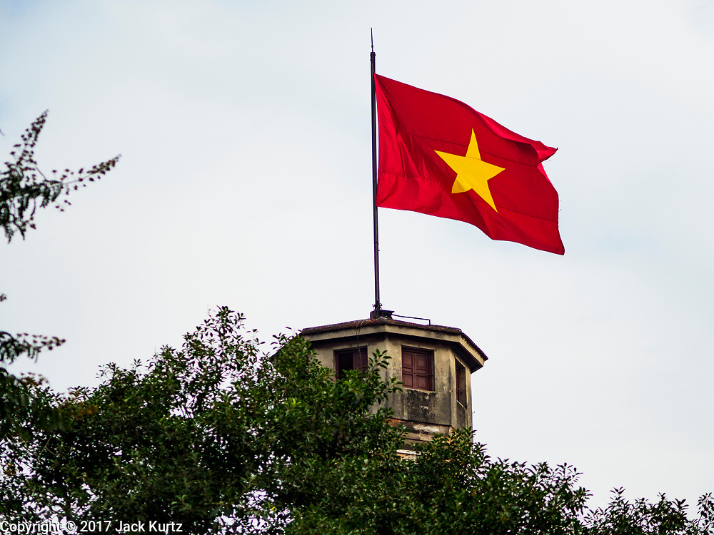 "21 DECEMBER 2017 - HANOI, VIETNAM: The Vietnamese flag flying from the ""flag tower."" The tower was built in 1812 during the Nguyen dynasty as an observation post to the Hanoi Citadel. Unlike many other structures in Hanoi, it was not destroyed during the French invasion (1896-1897), and was continuously used as a military post. It is now located in the Vietnam Military History Museum. PHOTO BY JACK KURTZ"