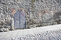 Ancient door by cobblestone street; Tallinn; Estonia; Europe