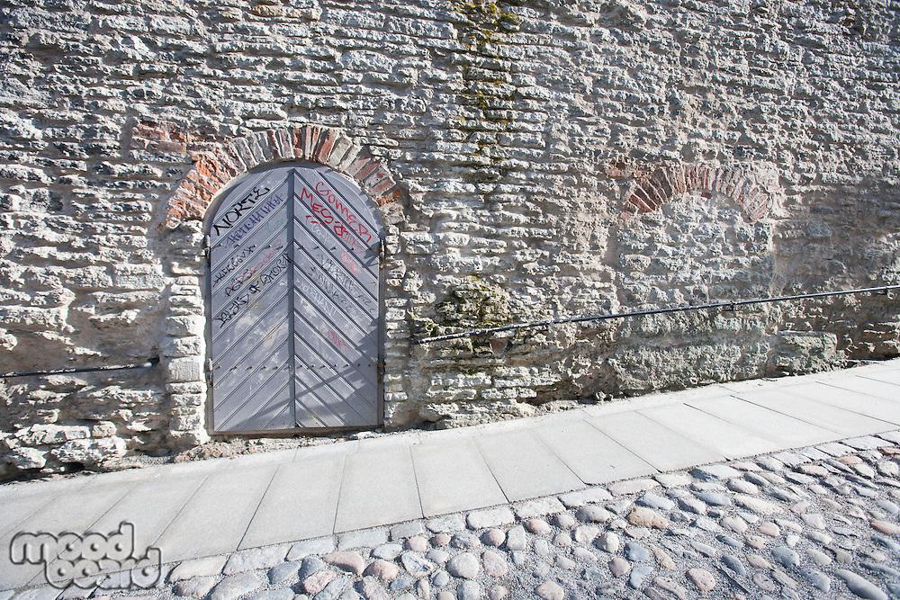 Ancient door by cobblestone street; Tallinn; Estonia; Europe