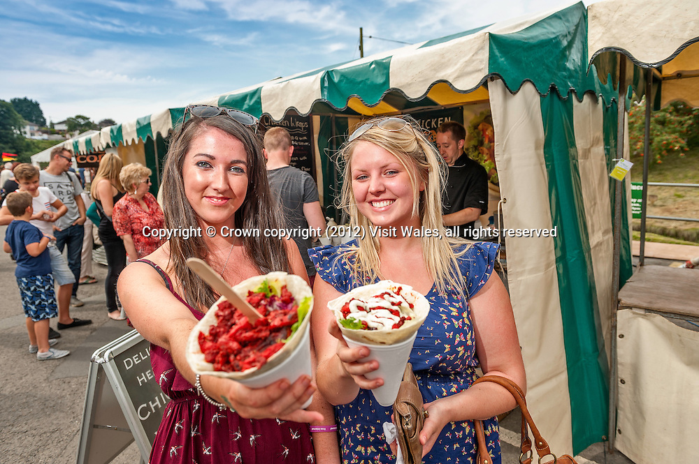 Two young women enjoying their food<br /> Cardigan River and Food Festival<br /> 2012<br /> Cardigan<br /> Ceredigion<br /> Mid<br /> Food<br /> Events
