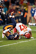 Denver Broncos defensive back Chris Harris Jr. (25) and Kansas City Chiefs tight end Travis Kelce (87) are upended as Harris breaks up a third quarter pass during the NFL week 4 regular season football game against the Kansas City Chiefs on Monday, Oct. 1, 2018 in Denver. The Chiefs won the game 27-23. (©Paul Anthony Spinelli)