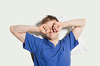 Young man rubbing eyes while waking up over colored background