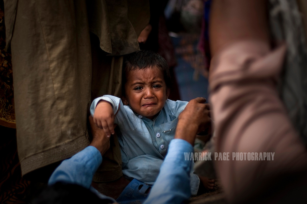 A flood-displaced child cries as he is placed onto the back of a truck with his family to feel rising floodwaters, on 14 September, 2011, in Khoski, Pakistan. More than 17% of children in the flood areas are severely acutely malnourished and 67% of livestock has been destroyed after torrential monsoon rains, reminiscent of the 2010 floods that devastated Pakistan, have reportedly already killed over 200 people, left 300,000 homeless and affected over 7 million. (Photo by Warrick Page)