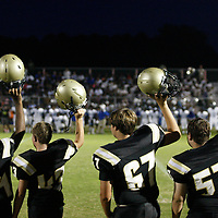 Amory football players lift their helmets in to the air at the start of the second quarter during Friday night's game against Aberdeen.
