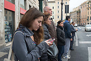 A woman studies her phone as people wait at a crosswalk in downtown Rome, Italy