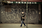 A woman walks in a street of Chinatown, New York, 2010.