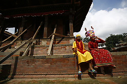 August 8, 2017 - Kathmandu, Nepal - Boys dressed in traditional attire sit in front of a temple during a procession to celebrate Gai Jatra or Cow Festival in Basantapur, Kathmandu, Nepal on Tuesday. People from the Newar community commemorate the festival to wish peace for their deceased family members from preceding years. (Credit Image: © Skanda Gautam via ZUMA Wire)