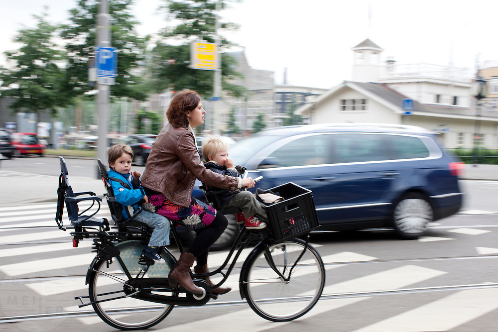 Een vrouw fietst met twee kinderen op de fiets door Rotterdam.<br /> <br /> A woman is cycling with two kids on her bike in Rotterdam.