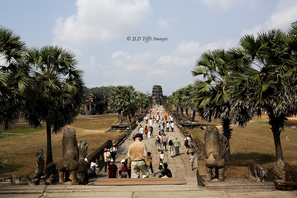 Angkor Wat, visitors exiting along the causeway toward the west gate or gopura, visible in the distance.