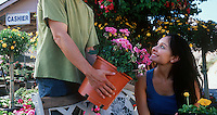 Man showing plant to woman in garden center