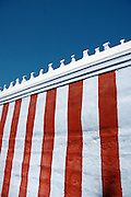 Red & white Hindu temple wall against Blue sky.
