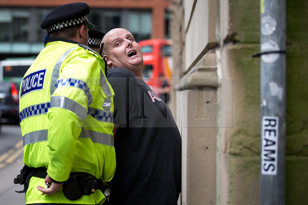 """© Licensed to London News Pictures . 22/08/2015 . Manchester , UK . A far-right supporter is detained by police . Far-right nationalist group , """" North West Infidels """" and Islamophobic , anti-Semitic and white supremacist supporters , hold a rally in Manchester City Centre . Photo credit : Joel Goodman/LNP"""