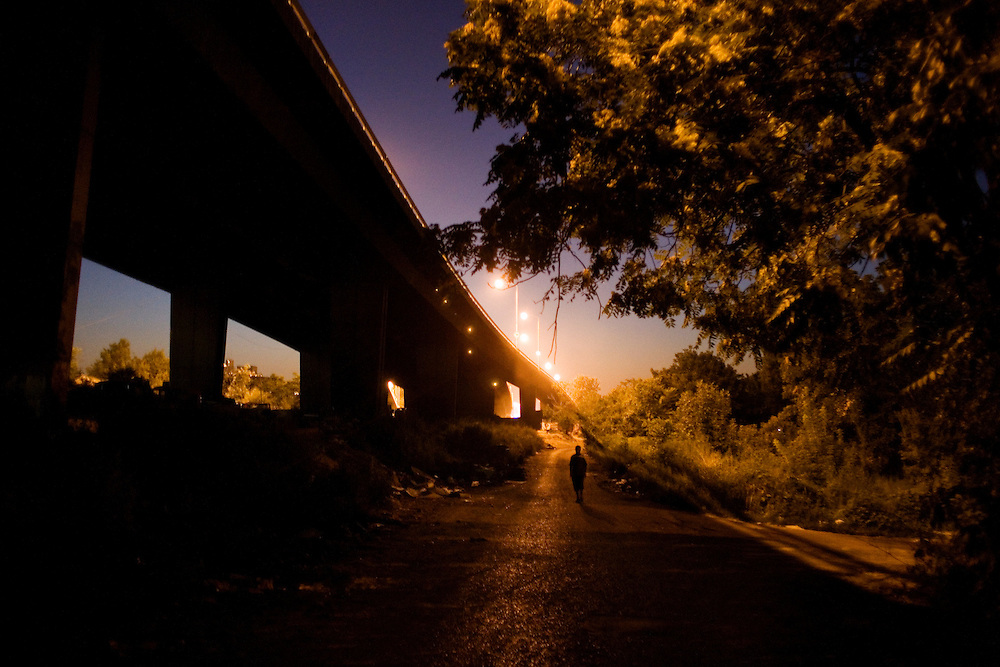 A lone figure walks along a parallel road to the Gazela Bridge at dusk outside of the Nova Gazela settlement.