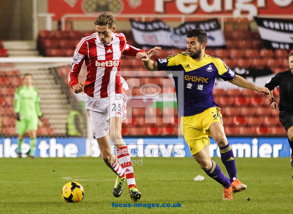 Peter Crouch (left) of Stoke City takes the ball away from Jordi Amat (right) of Swansea City during the Barclays Premier League match at the Britannia Stadium, Stoke-on-Trent<br /> Picture by Tom Smith/Focus Images Ltd 07545141164<br /> 12/02/2014