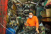 26 APRIL 2013 - BANGKOK, THAILAND:    A man works in his mechanical shop on a small street in Talat Noi. The Talat Noi neighborhood in Bangkok started as a blacksmith's quarter. As cars and buses replaced horse and buggy, the blacksmiths became mechanics and now the area is lined with car mechanics' shops. It is one the last neighborhoods in Bangkok that still has some original shophouses and pre World War II architecture. It is also home to a  Teo Chew Chinese emigrant community.      PHOTO BY JACK KURTZ