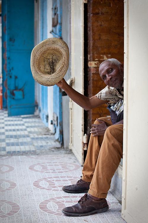 A man raises his hat in Les Cayes on the Tiburon Peninsula, Haiti