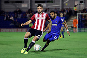 AFC Wimbledon striker Andy Barcham (17) battles for possession with Brentford defender Harlee Dean (6)during the EFL Cup match between AFC Wimbledon and Brentford at the Cherry Red Records Stadium, Kingston, England on 8 August 2017. Photo by Matthew Redman.