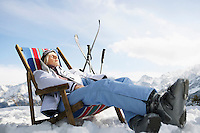Female skier resting on deckchair in mountains