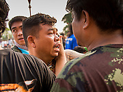 "15 MARCH 2014 - NAKHON CHAI SI, NAKHON PATHOM, THAILAND: Medics try to bring a man out of a trance state at the Wat Bang Phra tattoo festival. Wat Bang Phra is the best known ""Sak Yant"" tattoo temple in Thailand. It's located in Nakhon Pathom province, about 40 miles from Bangkok. The tattoos are given with hollow stainless steel needles and are thought to possess magical powers of protection. The tattoos, which are given by Buddhist monks, are popular with soldiers, policeman and gangsters, people who generally live in harm's way. The tattoo must be activated to remain powerful and the annual Wai Khru Ceremony (tattoo festival) at the temple draws thousands of devotees who come to the temple to activate or renew the tattoos. People go into trance like states and then assume the personality of their tattoo, so people with tiger tattoos assume the personality of a tiger, people with monkey tattoos take on the personality of a monkey and so on. In recent years the tattoo festival has become popular with tourists who make the trip to Nakorn Pathom province to see a side of ""exotic"" Thailand.   PHOTO BY JACK KURTZ"