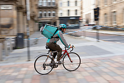 Deliveroo takeaway food delivery couriers on cycles in Glasgow city centre, Scotland, UK