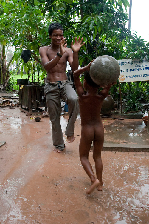BATTAMBANG, CAMBODIA: A young father plays football with his daughter under the rain near Battambang, Cambodia.