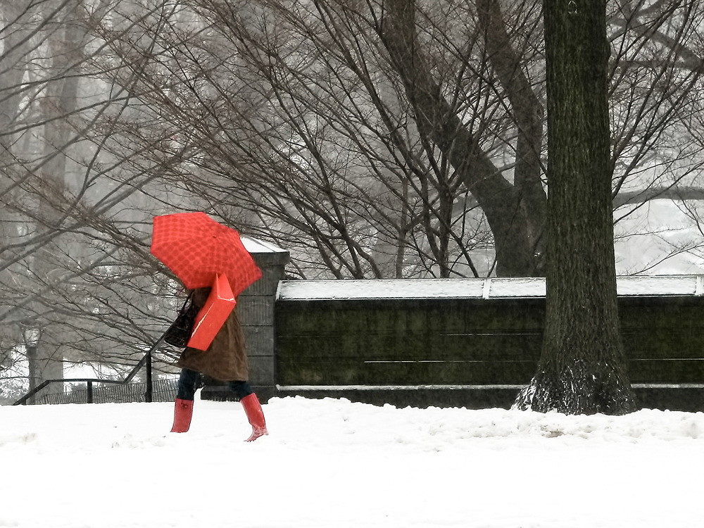 A one shot photo of woman in snow storm on 5th Av with red umbrella, red bag, red boots. NYC 2007