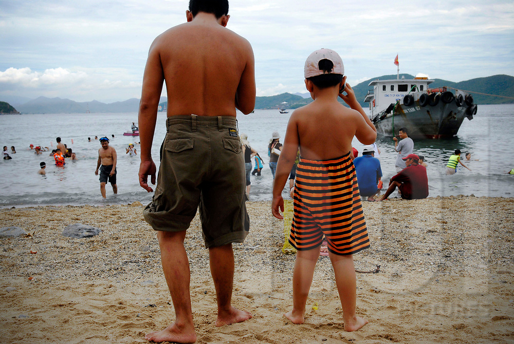Vietnamese family enjoy vacations on a beach of Nha Trang, Vietnam, Southeast Asia