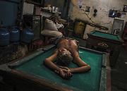 Brazil, Amazonas, rio Negro, Manaus. Fatigue, un marin en transit dort sur une table de billard.