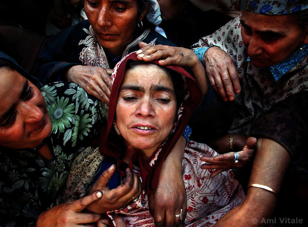 MIRHAMA, KASHMIR - SEPT. 21: Relatives of Naz Banu, who was killed during an attack on leading politician Sakina Yatoo, mourn over her body during her funeral in the northern Kashmir town of Mirhama, Saturday, Sept. 21, 2002. At least 11 people were killed and a second abortive bid was made to assassinate a leading woman politician Saturday, just days before a crucial second round of polls in the strife-torn northern Indian state of Jammu-Kashmir. (Photo by Ami Vitale/Getty Images)