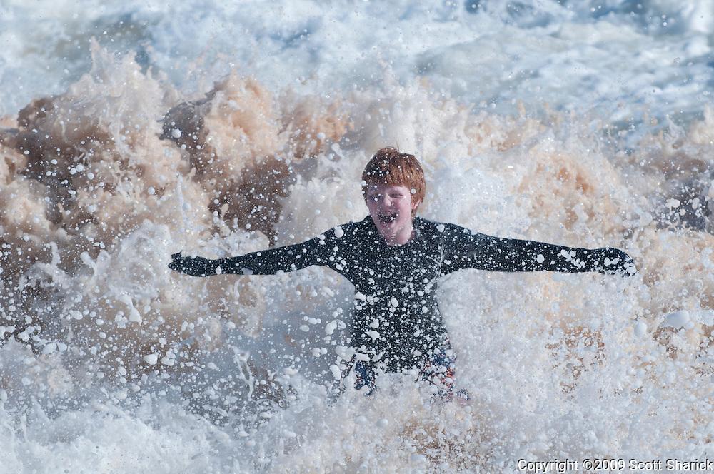 A wave engulfs a smiling boy at Sandy Beach on Oahu, Hawaii.