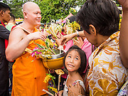 "22 JULY 2013 - PHRA PHUTTHABAT, THAILAND: A girl looks to her parents before presenting a monk with flowers during the Tak Bat Dok Mai at Wat Phra Phutthabat in Saraburi province of Thailand, Monday, July 22. Wat Phra Phutthabat is famous for the way it marks the beginning of Vassa, the three-month annual retreat observed by Theravada monks and nuns. The temple is highly revered in Thailand because it houses a footstep of the Buddha. On the first day of Vassa (or Buddhist Lent) people come to the temple to ""make merit"" and present the monks there with dancing lady ginger flowers, which only bloom in the weeks leading up Vassa. They also present monks with candles and wash their feet. During Vassa, monks and nuns remain inside monasteries and temple grounds, devoting their time to intensive meditation and study. Laypeople support the monastic sangha by bringing food, candles and other offerings to temples. Laypeople also often observe Vassa by giving up something, such as smoking or eating meat. For this reason, westerners sometimes call Vassa the ""Buddhist Lent.""     PHOTO BY JACK KURTZ"