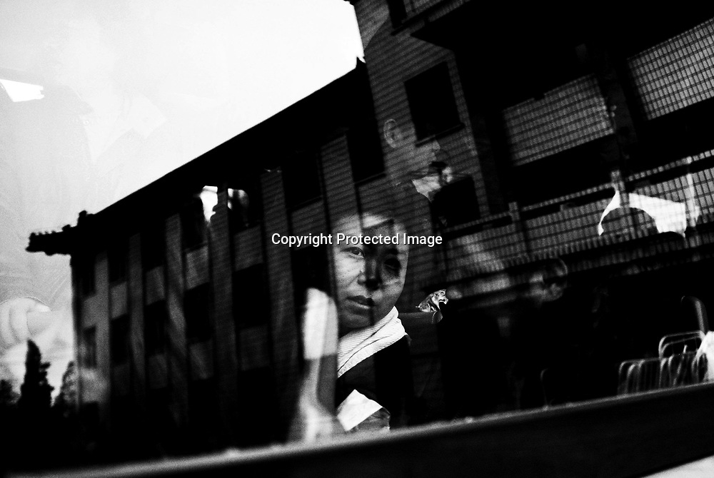 BEIJING,NOV.10:  a female schizophrenic patient talkes leave of her former home, a privately-run mental institution  is reflected in the bus window.The hospital had to move to the suburbs as they could not afford the rent anymore.Besides,the old location is part of a newly designed ecomic zone..
