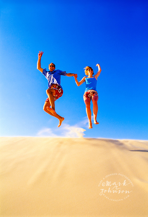 Australia --- Couple Holding Hands while Jumping from Sand Dune