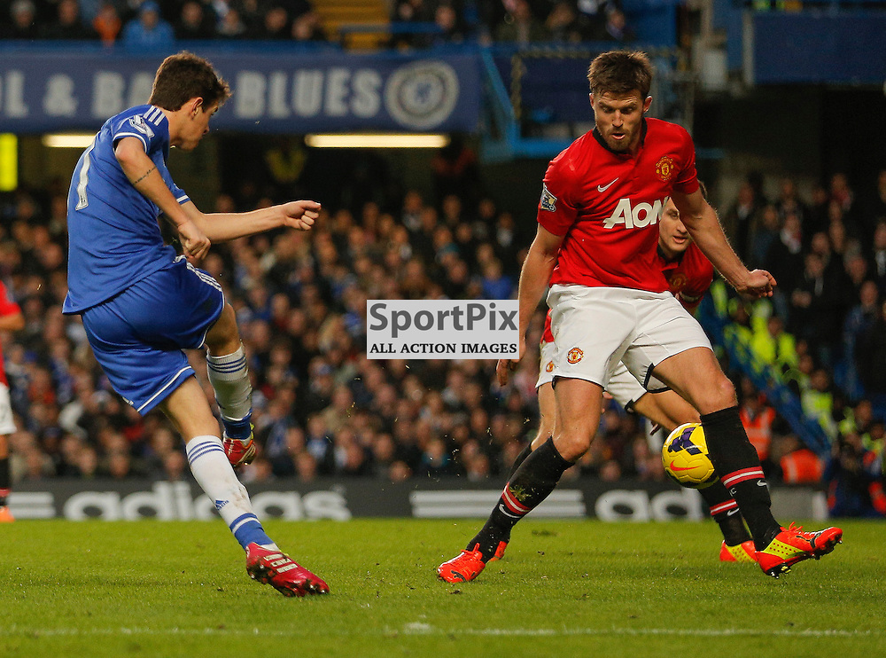 Chelsea MF 11 Oscar lets fly with a shot that goes between Manchester United MF 16 Michael Carrick and DF 15 Nemanja Vidić (C) | Andy Walter (c) Sportpix.org