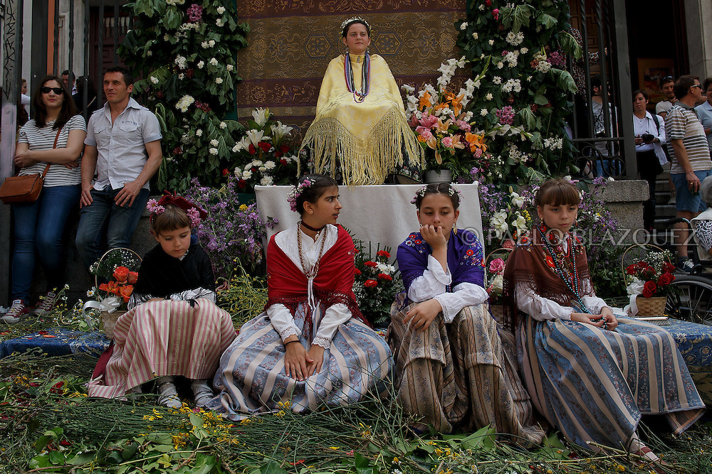 A 'Maya' sits on the altar as others sit around during the 'La Maya' tradition in the streets around the San Lorenzo church on May 10, 2015 in Lavapies neighborhood, Madrid, Spain. 'La Maya' festivity is a pagan tradition to celebrate the beginning of the spring which is believed to come from the medieval age. In old times the 'Maya's Festival' used to take place at The 'Mayas' field' (Prado de las Mayas) which is where now the San Lorenzo church is located. La Maya combines symbols of fertility and prosperity on agriculture and shepherding economy. A 'Maya' girl dressed with traditional customs sits on an altar in the street decorated with flowers, plants and cushions. Other Mayas and Mayos offer flowers, traditional sweets, lemonade, and wine to members of the public as they play music and dance. (© Pablo Blazquez)