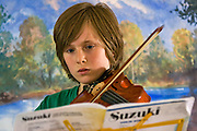 One of Andy Mackie's methods is for children to lead and teach other children.  This young violinist is leading a class in an exercise.